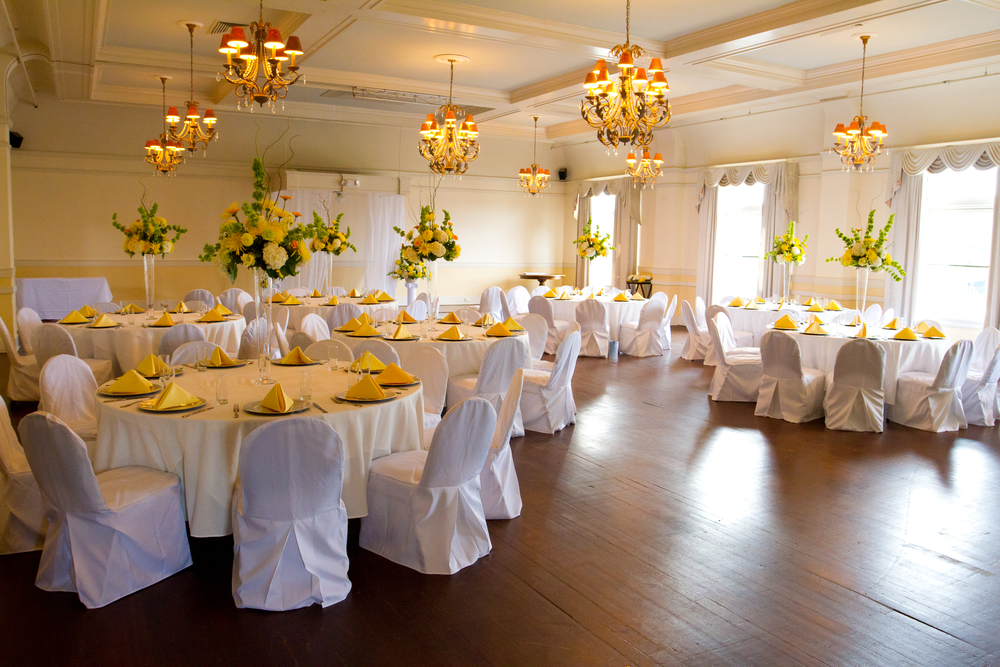 Place settings, tables, and chairs are empty before the guests arrive at a wedding reception.